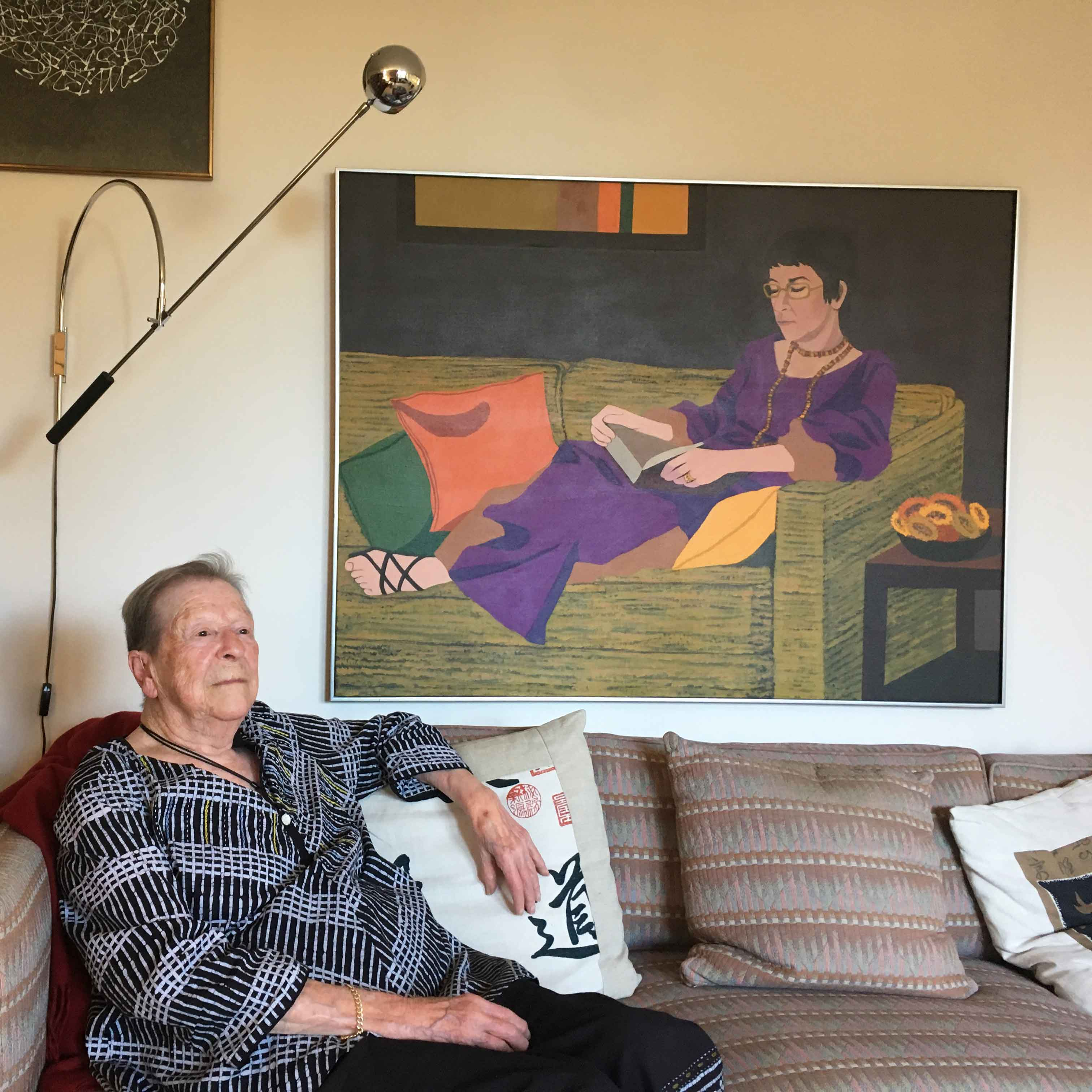 Professor Angela Little sits on a couch in front of a painting