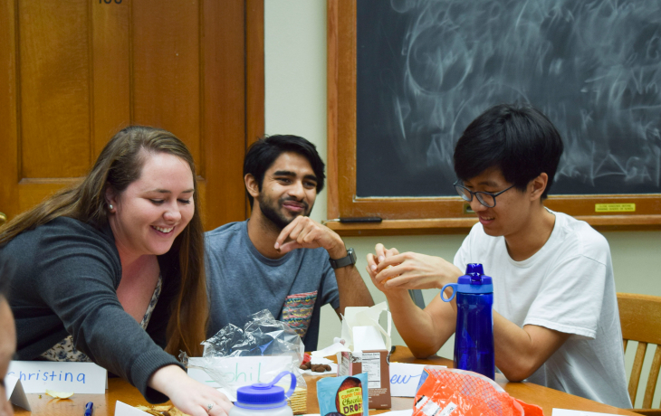 A student reaches across a table with two other students to her right