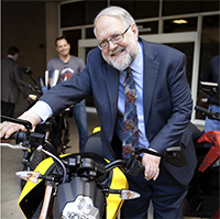 Robert Weisenmiller test-drives a Zero Motorcycle at the Plug-In Electric Vehicle Showcase in 2013.