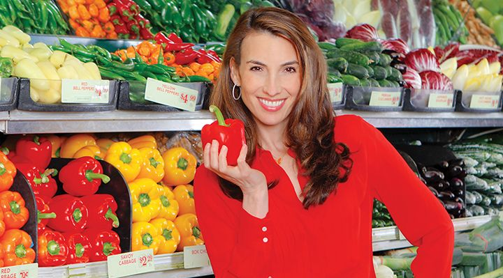 A woman holding a bell pepper in a grocery store