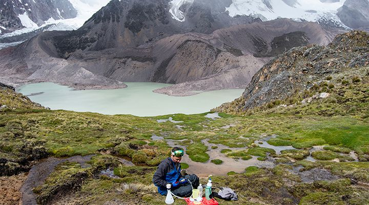 A researcher gathering samples near a beautiful lake by mountains