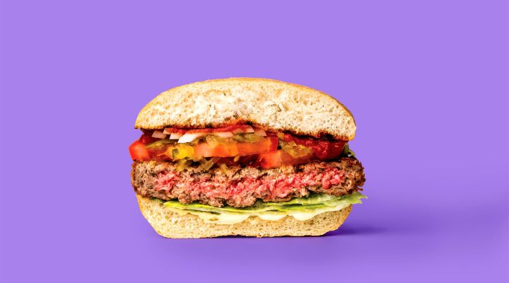 A cross section of a hamburger against a purple backround