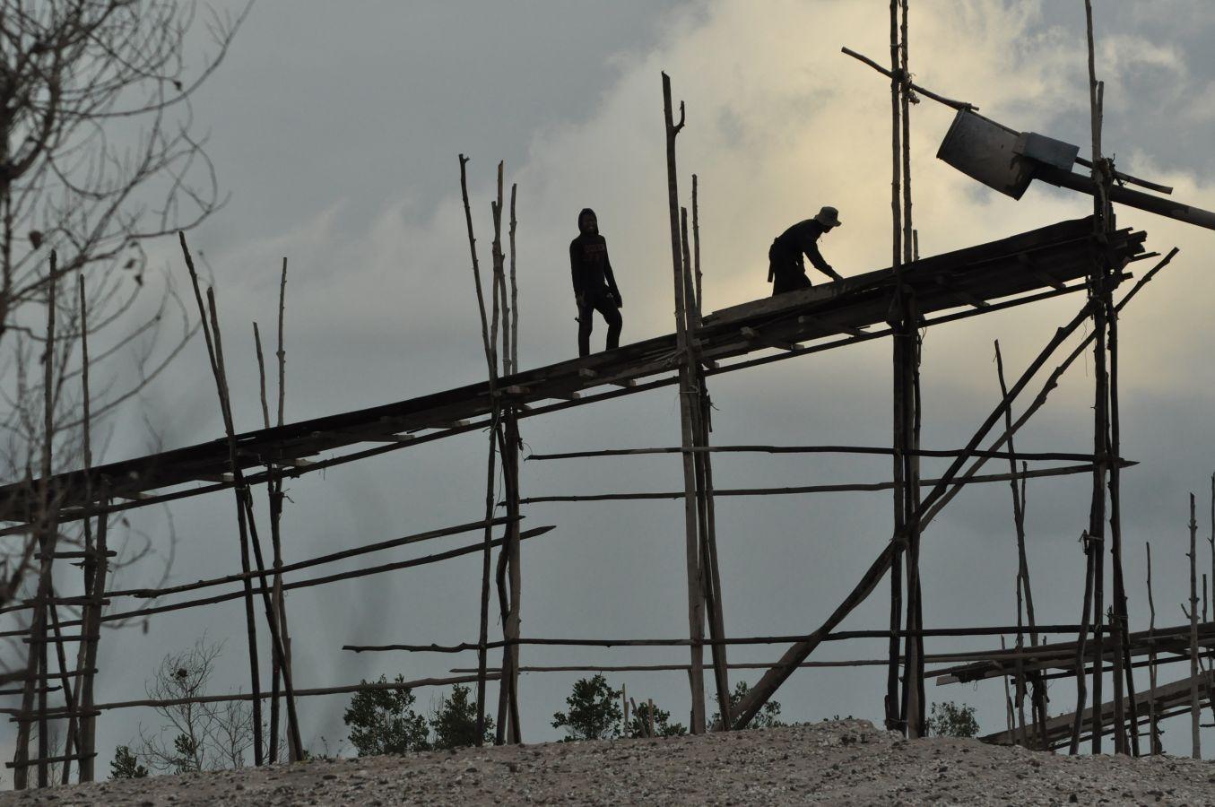 Miners preparing a wooden sluice structure
