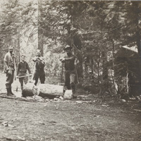 Forestry campers chop wood for the camp cook, 1920.