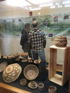 a man and woman with backs to camera examine a Karuk Tribe geographical history poster. Baskets in foreground.