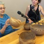 At right, a woman in a black sleevless top sits at microphone with pen and pad. At lef, a woman in a blue shirt sits at second mic holding a deep bowl-shaped woven tribal basket. Three other baskets in different sizes are on the table in front of them.