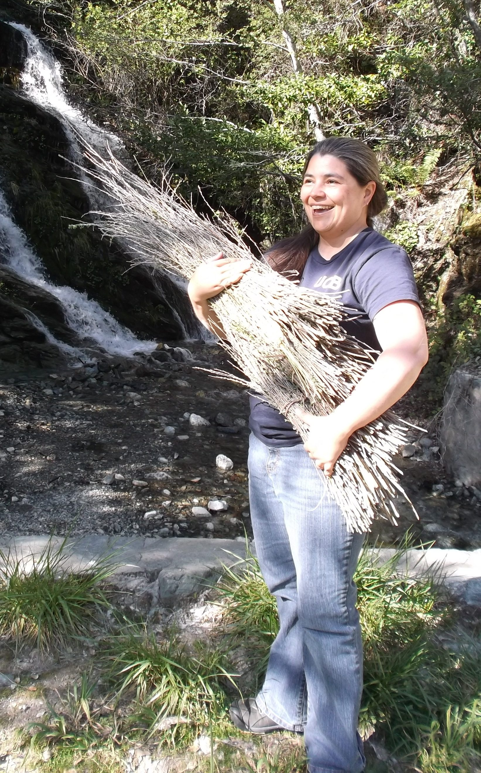 Carolyn Smith stands in front of a tree on a grassy area holding a sheaf of fiber used for basketry