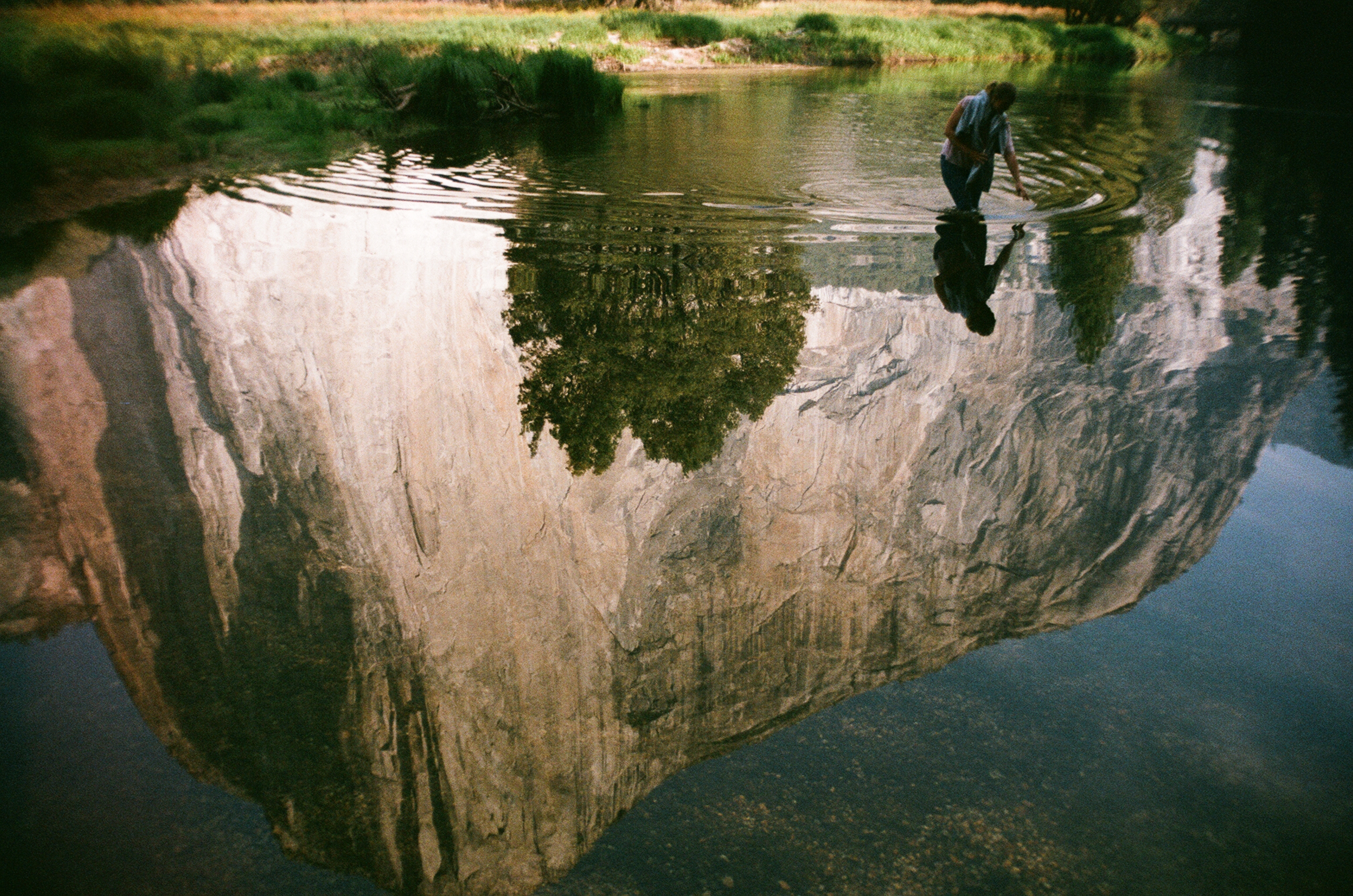 Reflection of a person and a mountain in water