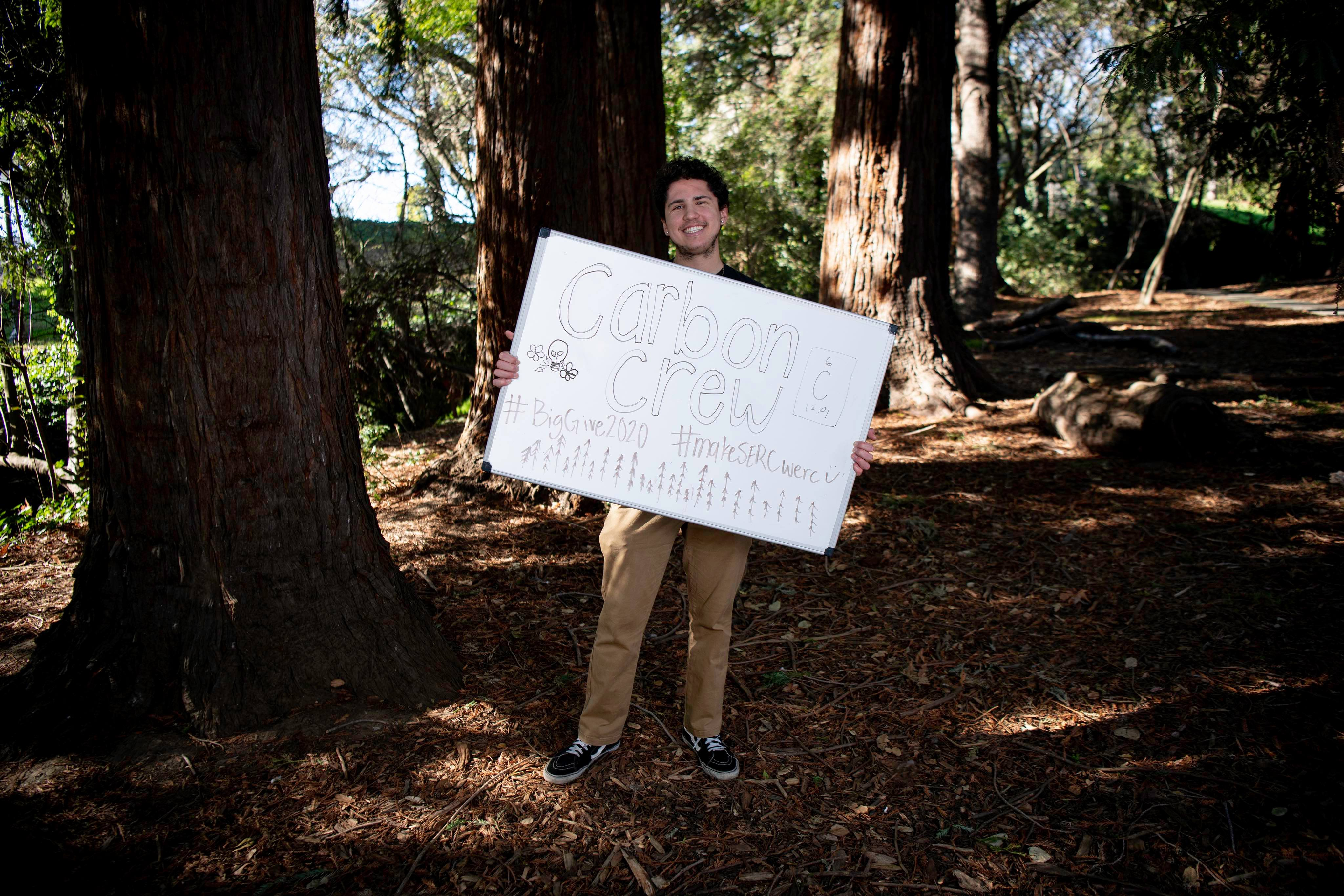 Dante holding a sign about SERC in front of a tree.