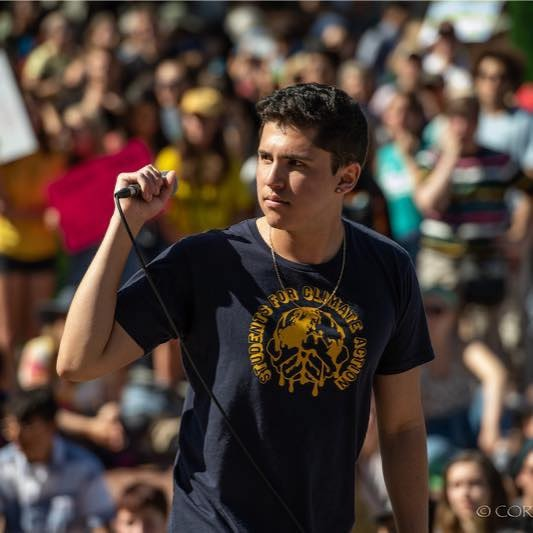 Dante Gonzalez holding a microphone in front of a crowd.