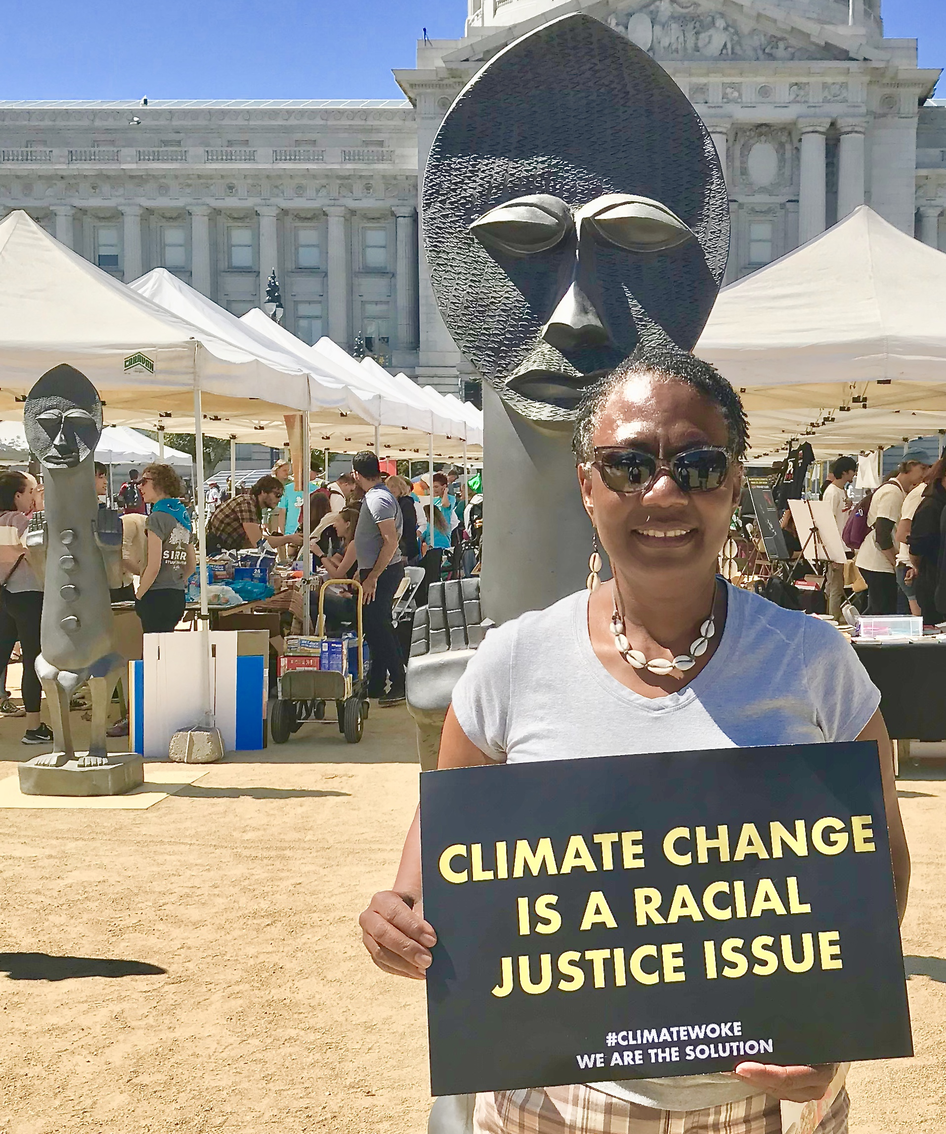 """Violet Henderson holding a sign saying """"climate change is a racial justice issue."""""""