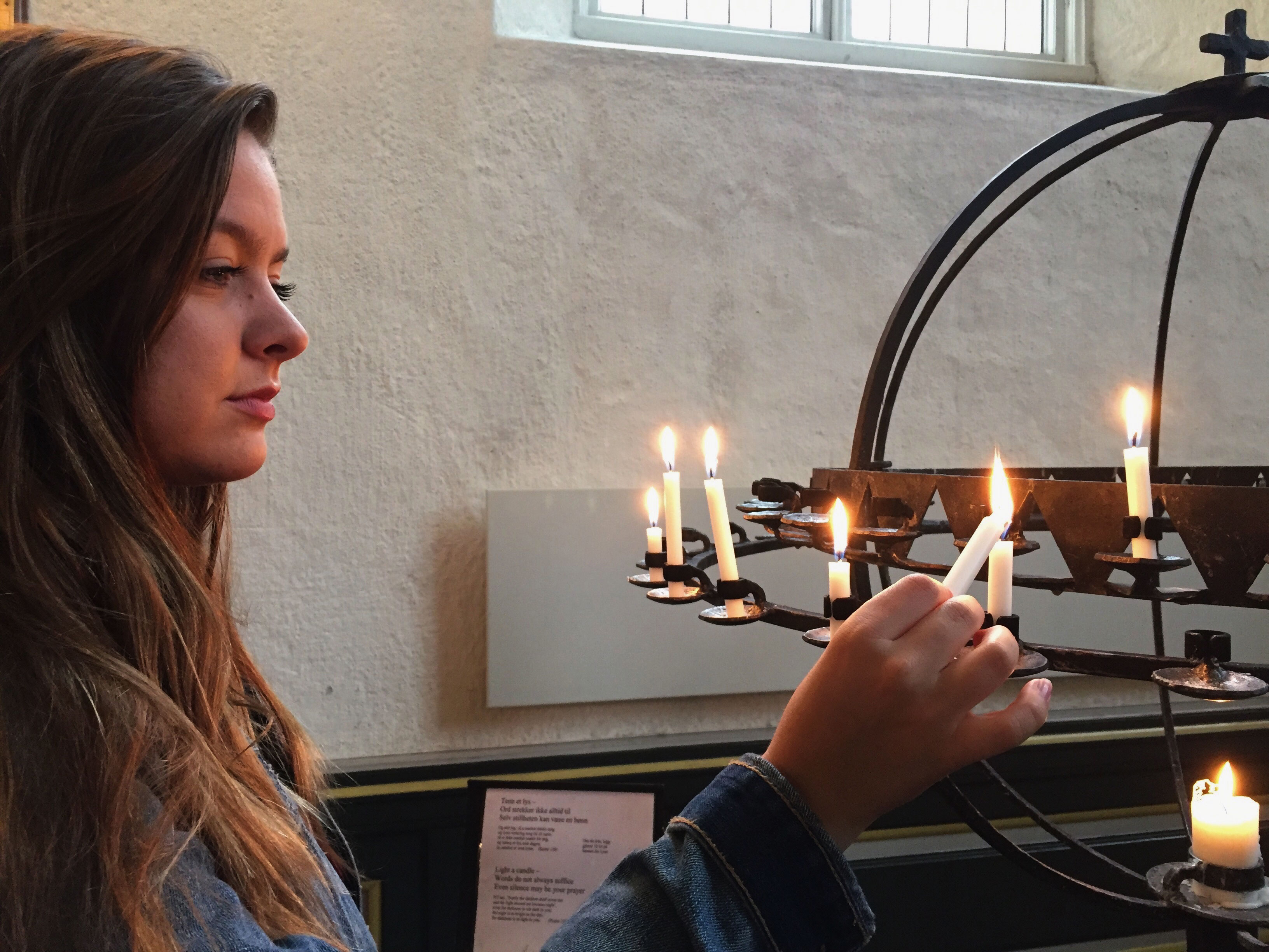 A student lights a candle in a church