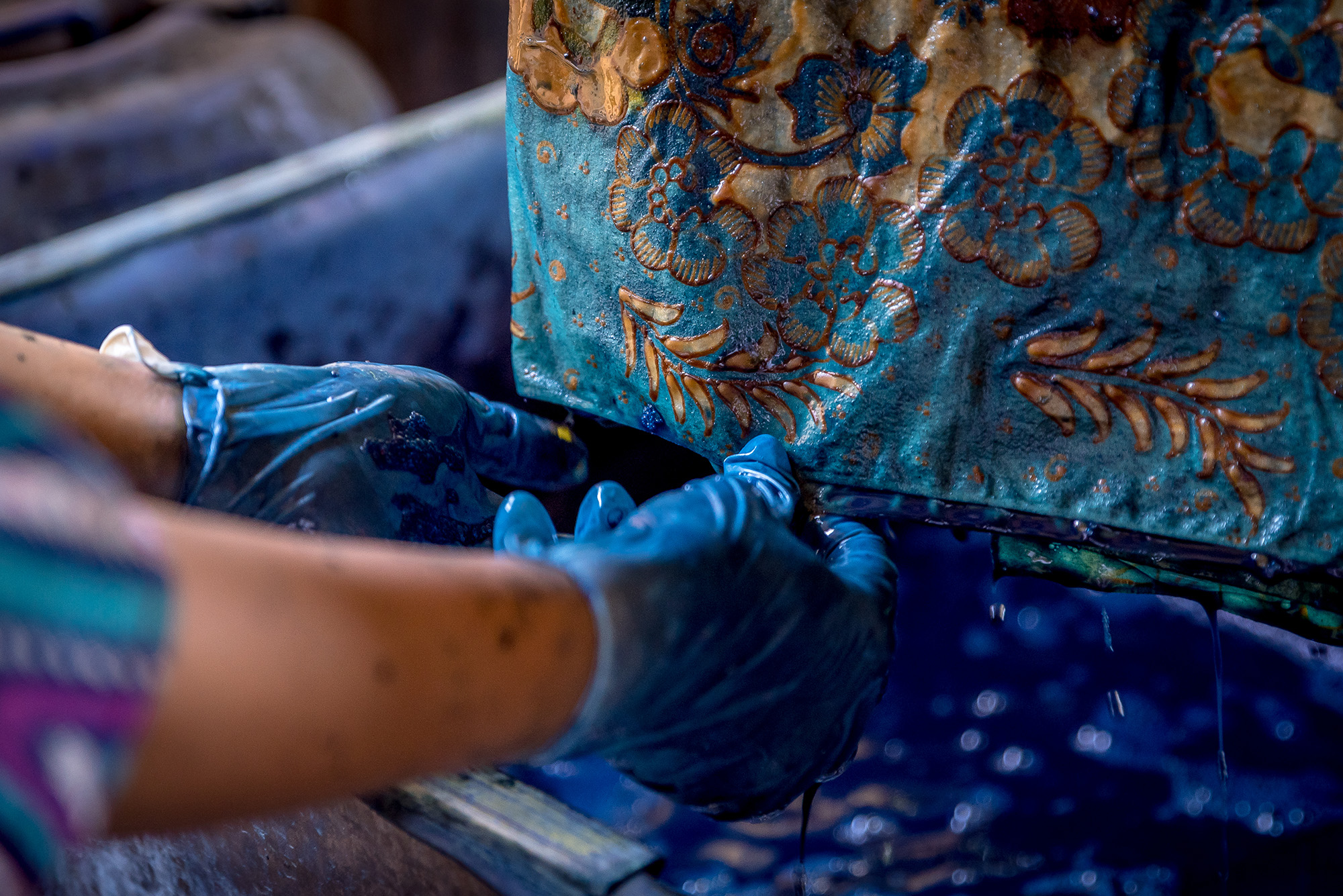 Hands in blue gloves holding fabric, both dripping in dye