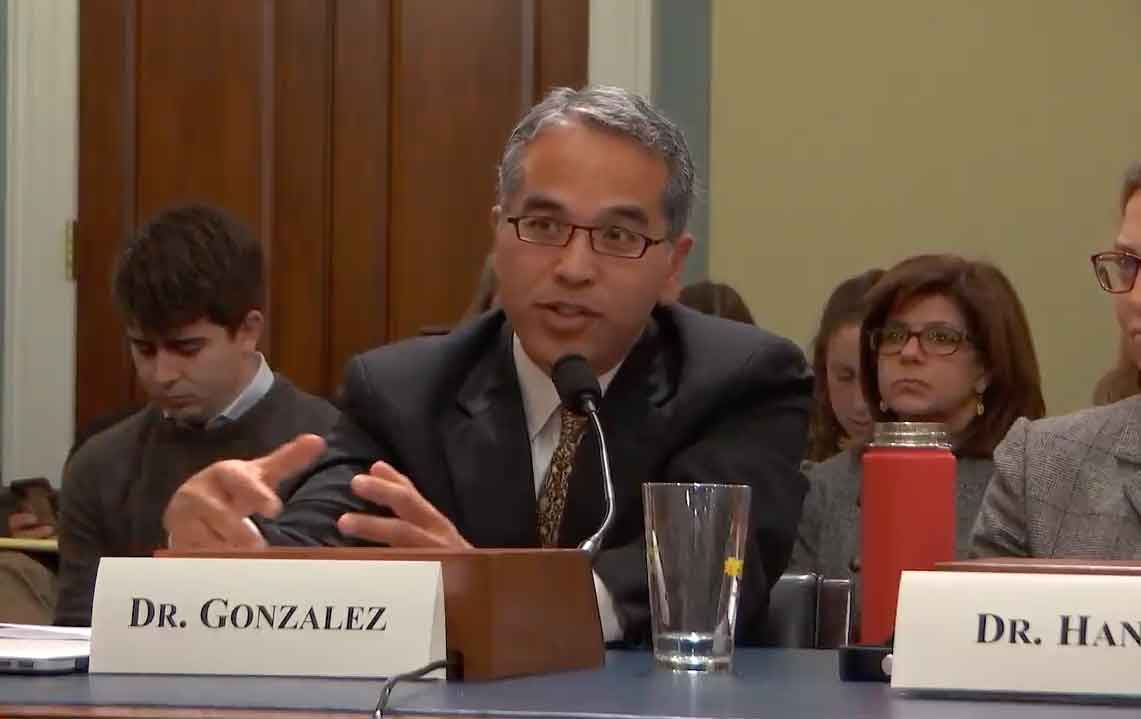 A man sits at a table in front of a microphone to testify in front of congress