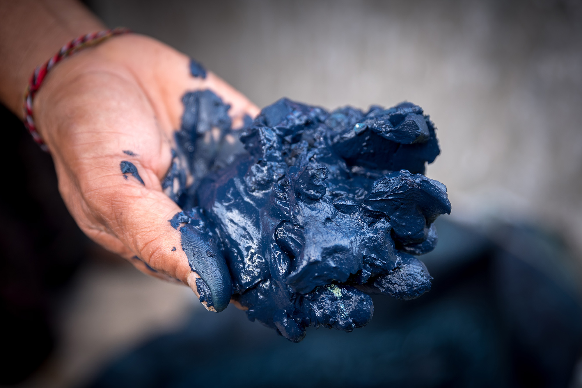 A hand with a string bracelet holds out indigo dye paste, which looks like wet, blue clay.