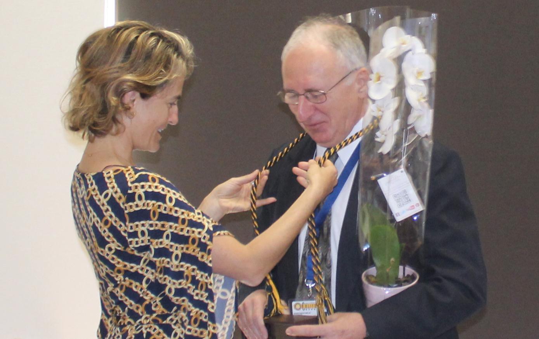 Professor Sofia Villas-Boas placing an honors cord around Professor Anastasios Melis' neck at honors research symposium