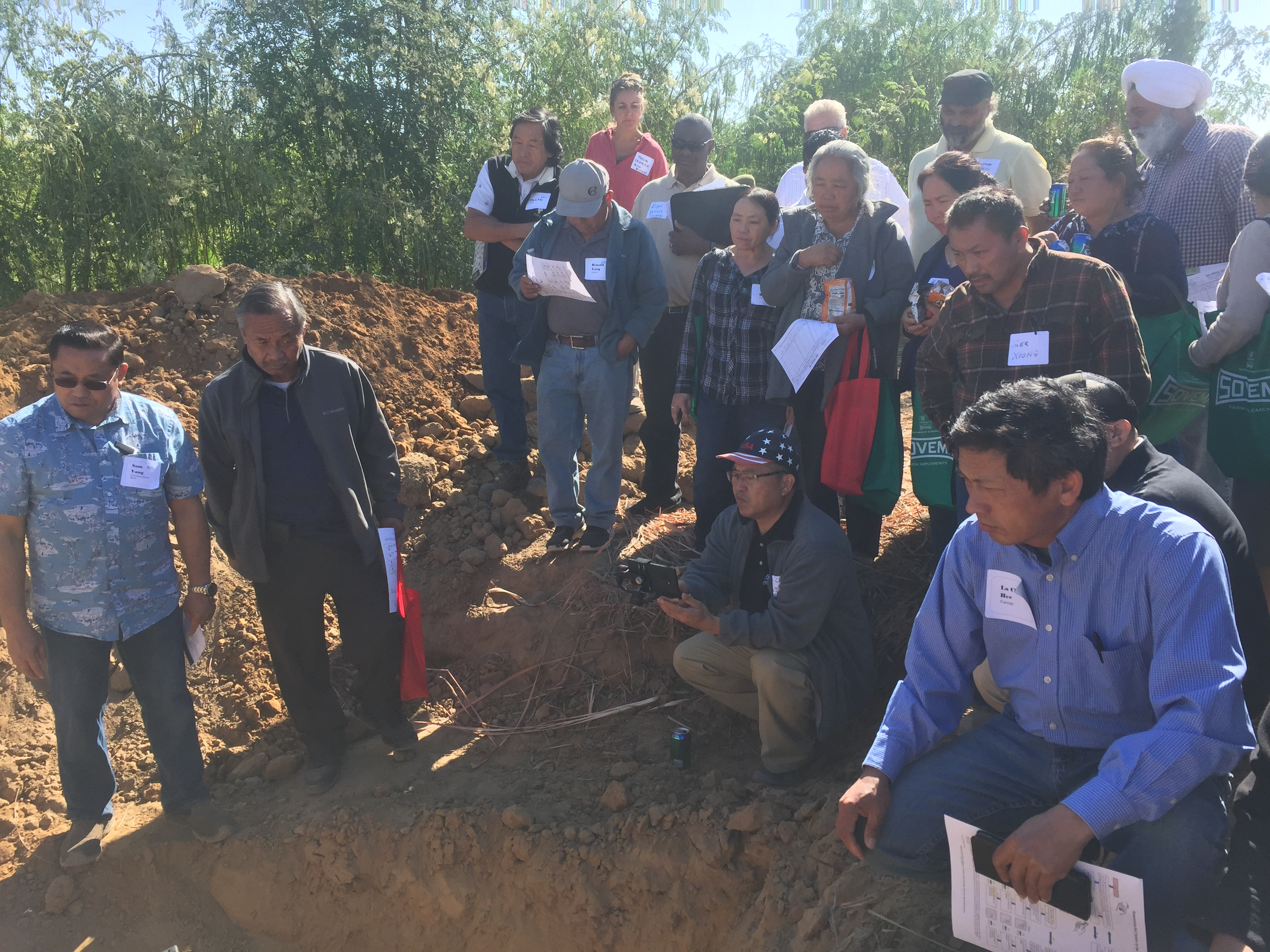 Soil pit demonstration in NRCS led workshop in Fresno County with many participants watching on.
