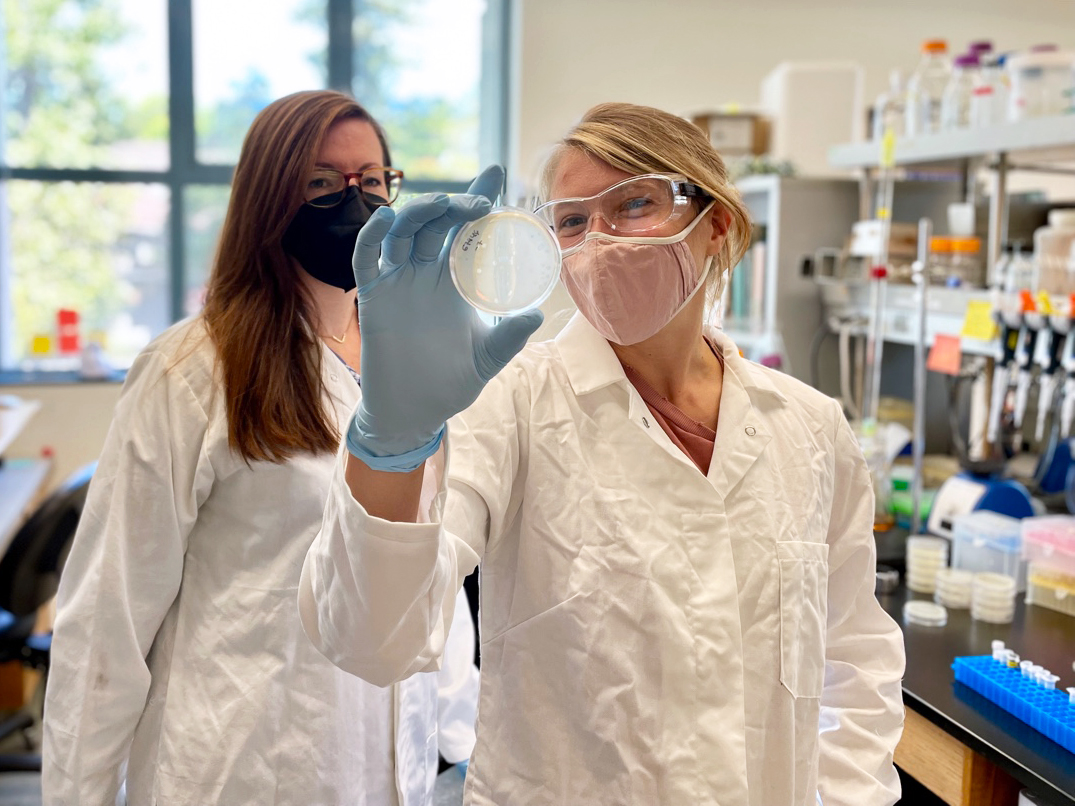 Two researchers wearing masks holding up a petri dish