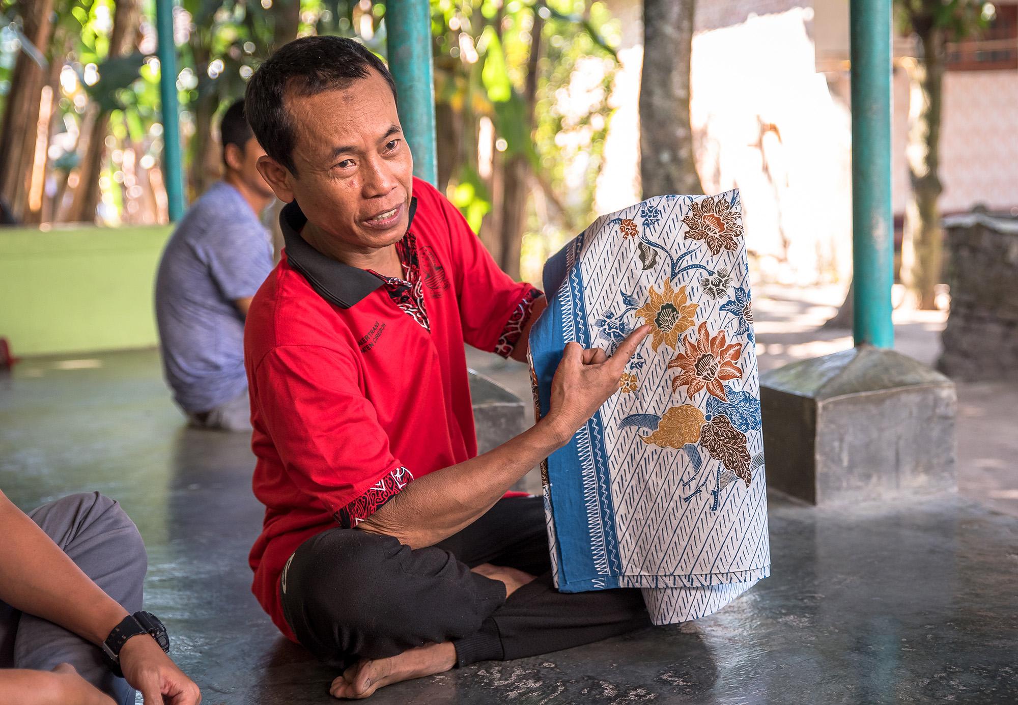 Man sitting, holding blue batik.