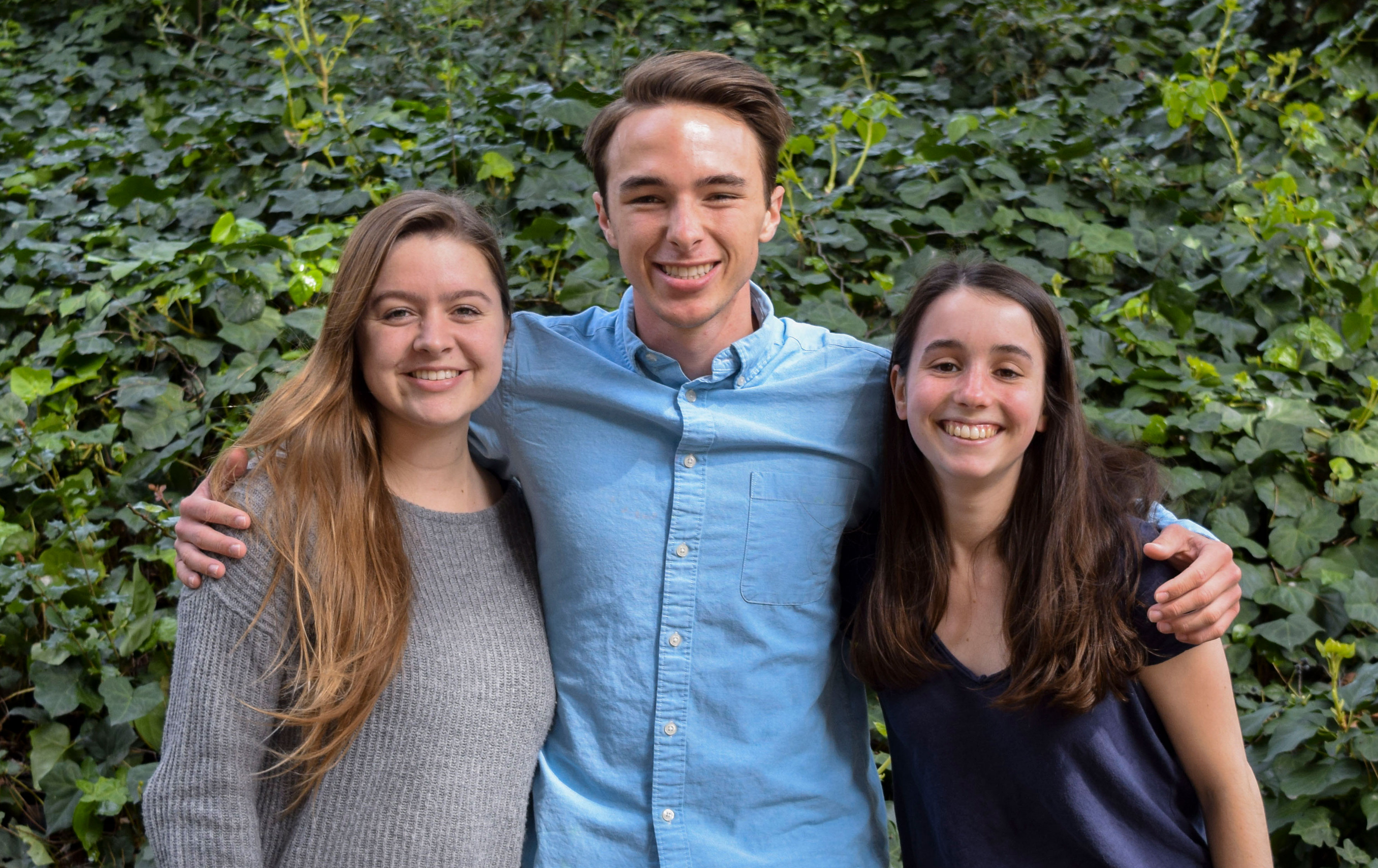 Three students standing together and smiling at camera