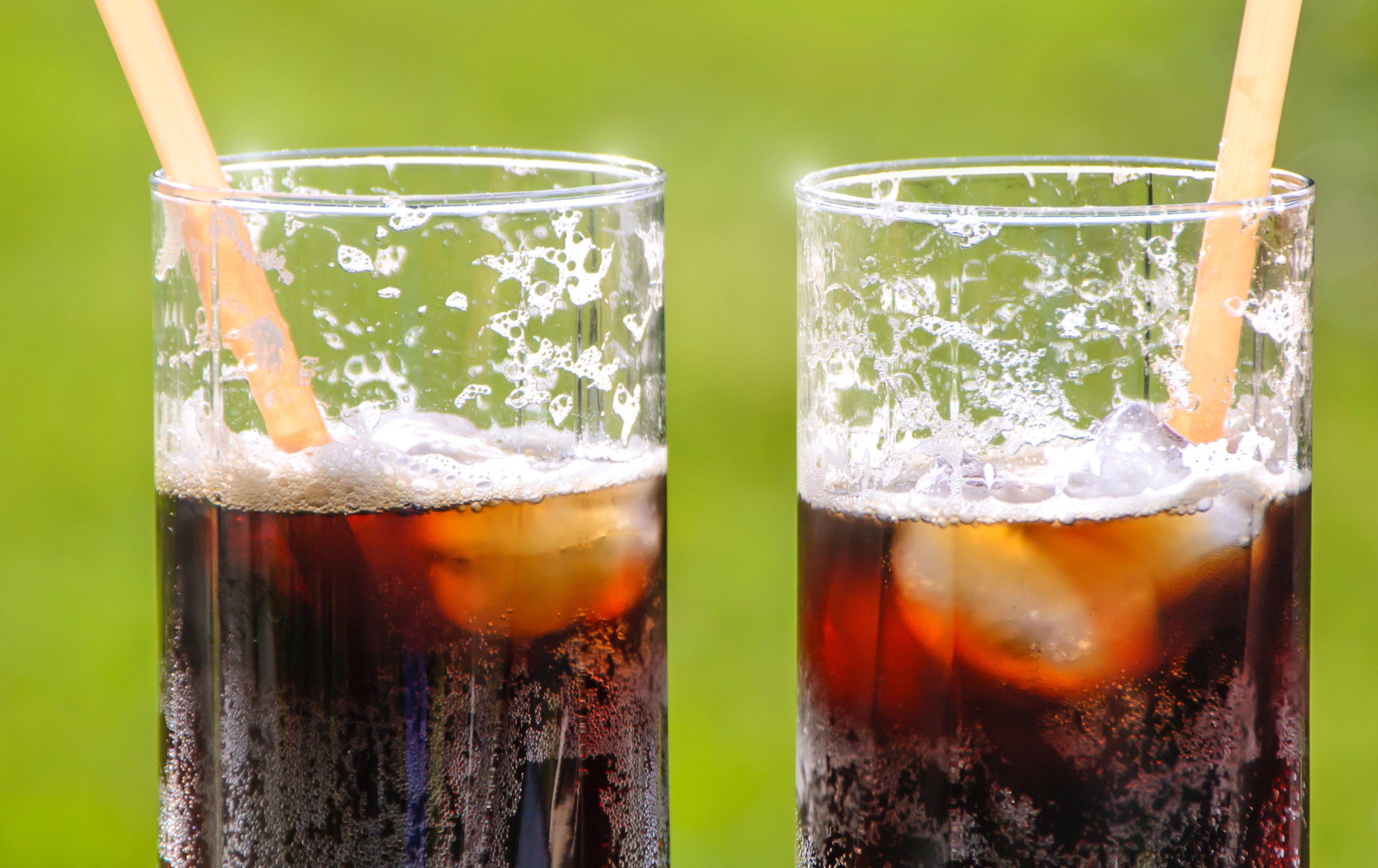 Two glasses with ice and unidentifiable soda in them.
