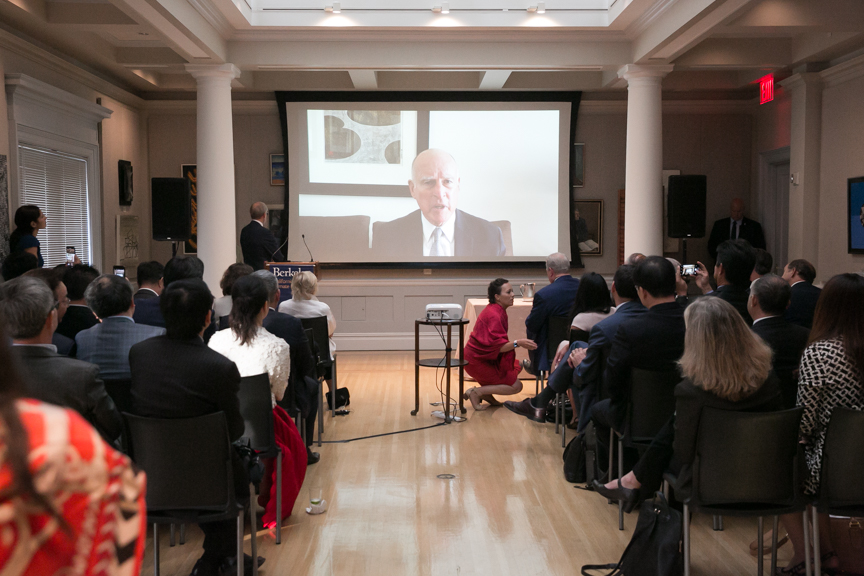 Jerry Brown addressing an audience on a video screen