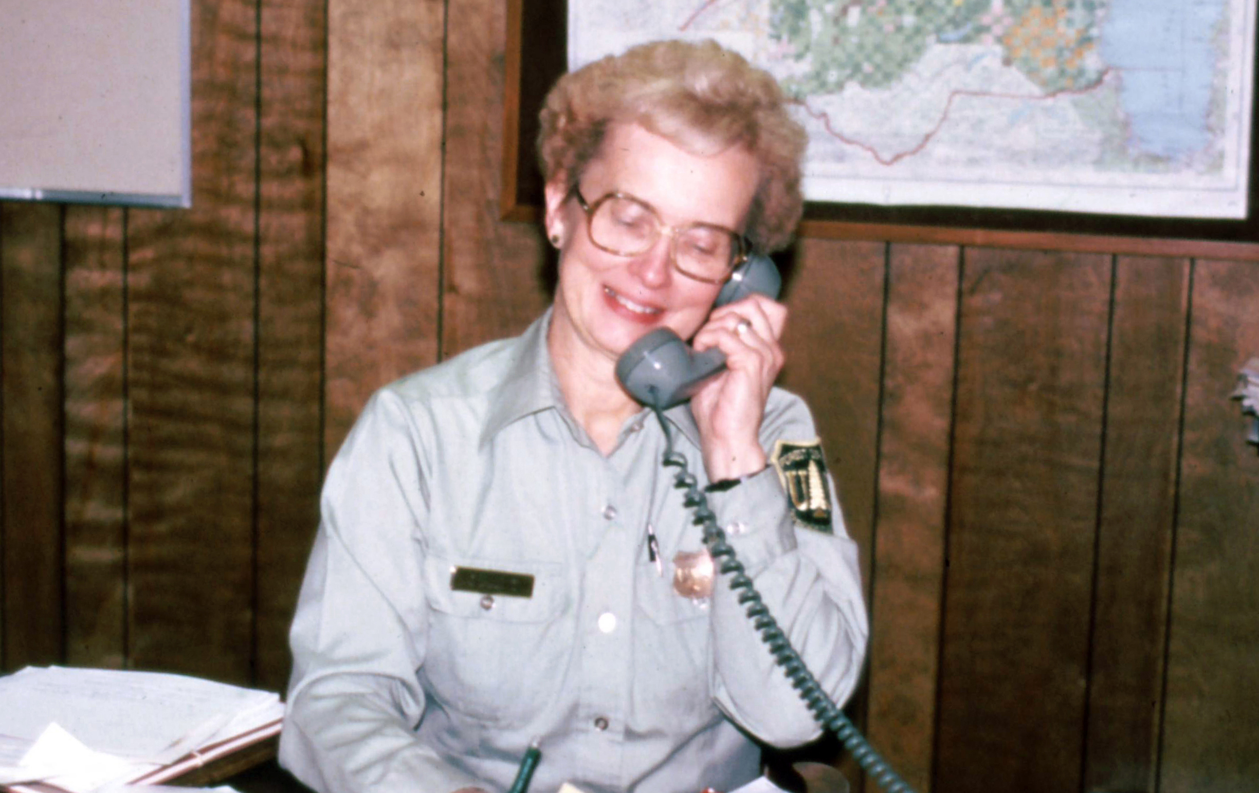 Geri Bergen sitting at a desk with papers around her. She is on the phone.