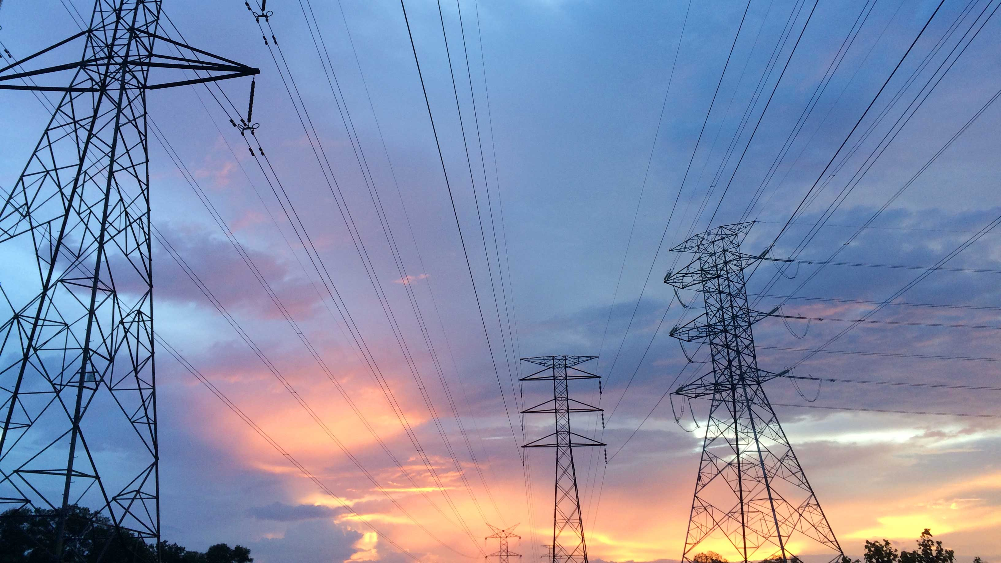 a colorful sunset with electrical grid towers in the foreground