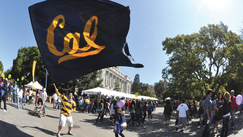 Student waving Berkley flag on Cal Day