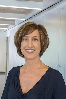 Susan Hubbard smiling in a hallway