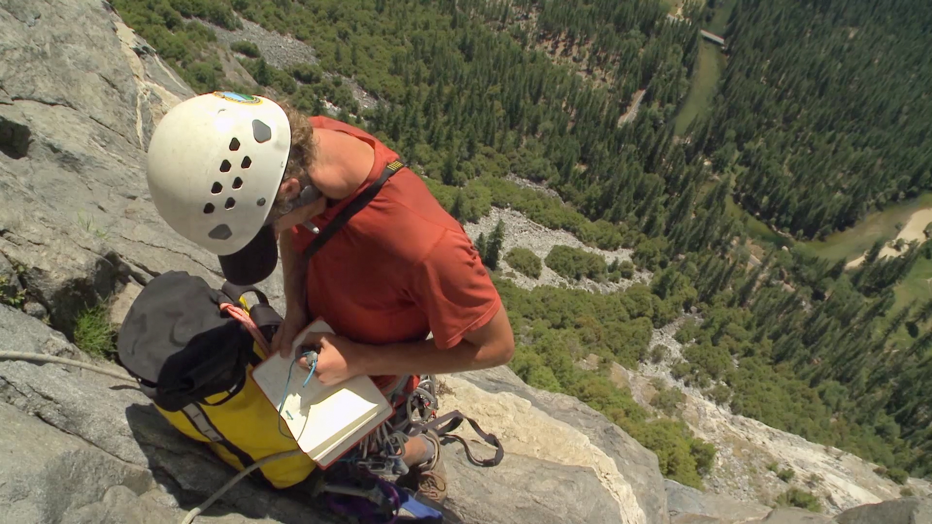 Rock climber taking notes in field journal