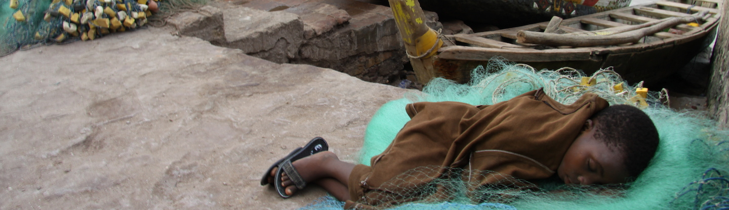 young boy sleeping on fishing net