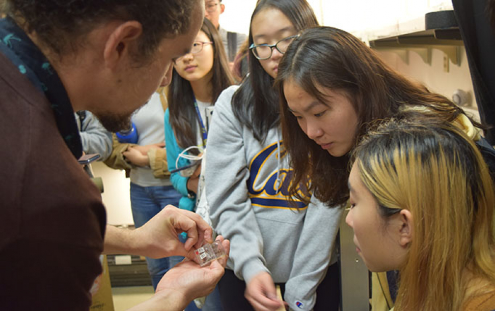 PhD candidate Ignacio Escalante shows the students tiny spiders during a lab tour