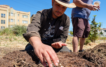 A man sowing seeds into the dirt.