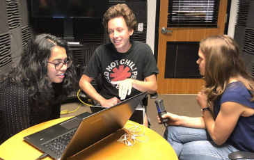 Three students recording an episode of the podcast
