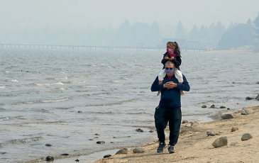 A person with their child on their shoulders on the beach.