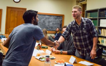 Two men stand to shake hands in a classroom