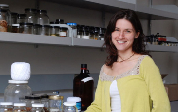 Bree Rosenblum stands next to jars in a lab