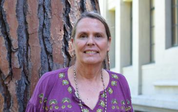 Lynn Huntsinger in a purple shirt in front of trees.