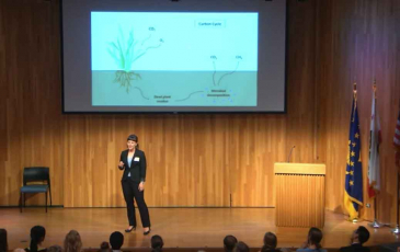 A woman stands on a stage in a suit, presenting to an audience in front of a PowerPoint slide
