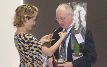 Professor Sofia Villas-Boas placing an honors cord around Professor Anastasios Melis' neck at honors research symposium