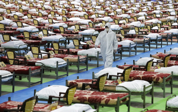 Empty hospital beds in Iran and a worker in full protective equipment