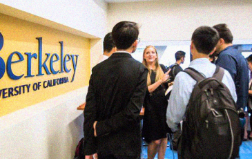 A woman speaking to two students next to a Berkeley sign.