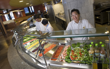 Workers standing behind an organic salad bar in a campus cafeteria