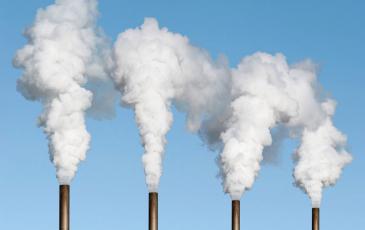 four smoke stacks against a blue sky