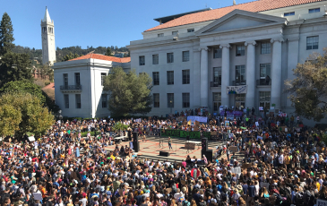 A crowd in front of Sproul Plaza for the Climate Strike. A woman is on a stage and the Campanile is in the background.