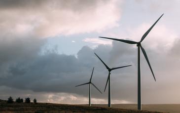 Three wind turbines standing in a flat field, under cloudy skies.