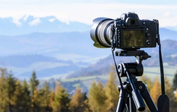 A camera on a tripod facing a mountain range