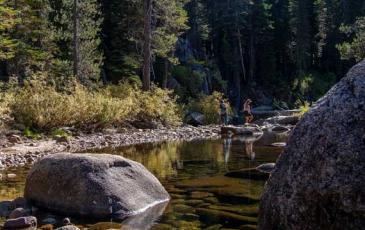 A woman walks across a river