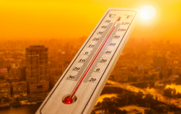 Thermometer in front of cityscape
